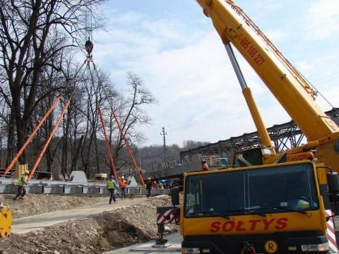 Dźwig rozpoczyna unoszenie pierwszej części konstrukcji mostu