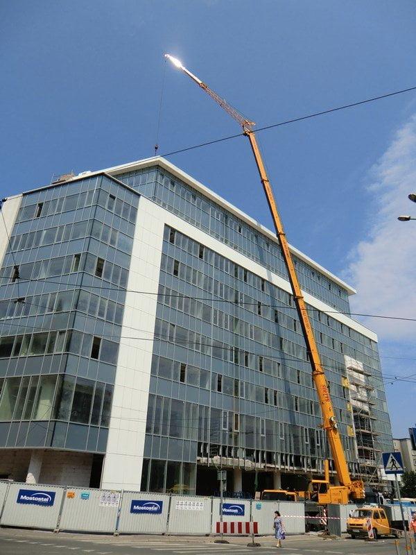 Dźwig firmy Sołtys w trakcie montażu elementów dużego budynku w Katowicach.